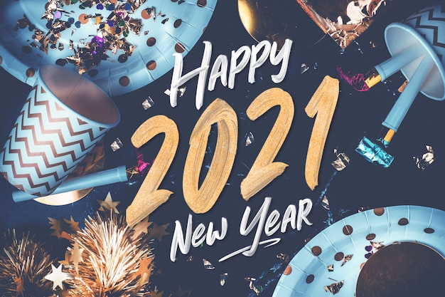 2021 happy new year hand brush stroke on marble table with party cup,party blower,tinsel,confetti