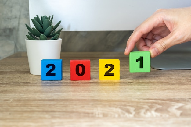 2021 happy new year, hand holding wood block on wood table desktop computer and pot plant. new year concept
