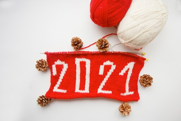 2021 happy new year. knitted number. skeins of yarn and pine cone.