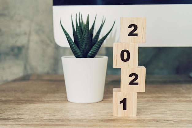 木製テーブルデスクトップコンピューターと鉢植えの木版画の2021年明けましておめでとうございます。新年のコンセプト