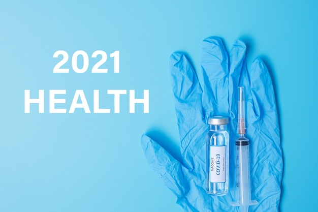 2021 happy new year with covid-19 vaccine vial and injection needle syringe against coronavirus