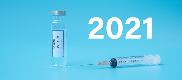 2021 happy new year with covid-19 vaccine vial and injection needle syringe