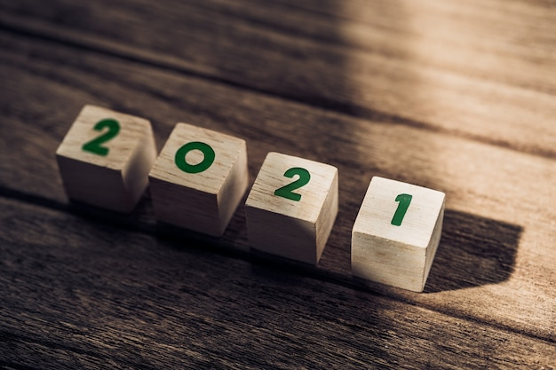 2021 happy new year on wood block on wood table and concrete wall with sunlight from window.