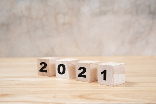 2021 happy new year on wood block on wooden table ang grey background. new year concept.