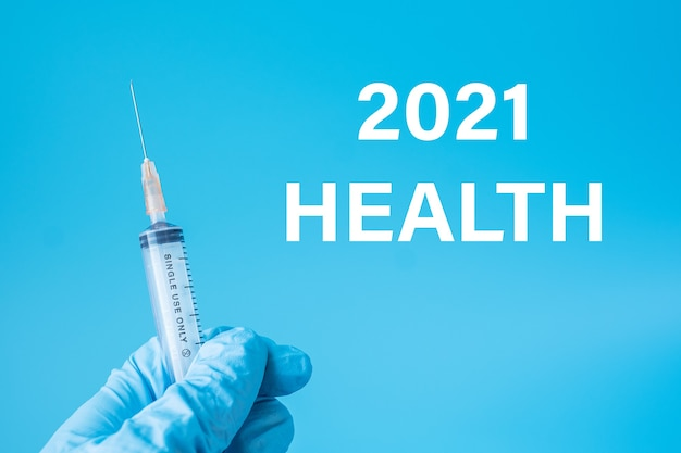 2021 health with hand of doctor injection vaccine or drug by needle syringe on blue