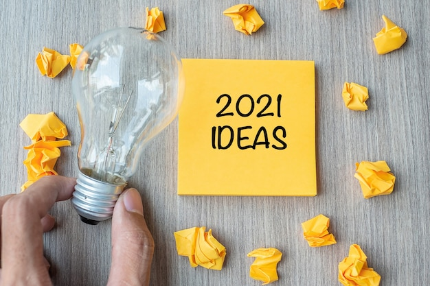 2021 idea words on yellow note and crumbled paper