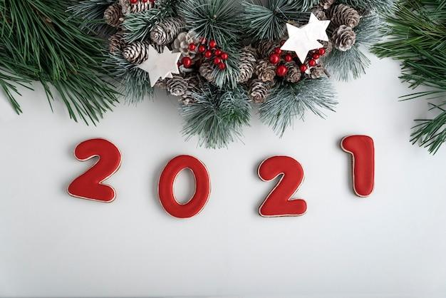 2021年の碑文とクリスマスリース、上面図。白色の背景。明けましておめでとうございます2021。