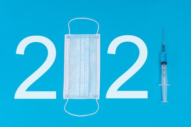 의료용 마스크와 백신 주사기로 만든 2021 로고. 2021 년 유행병과 약물 방출의 상징으로. 파란색 배경.