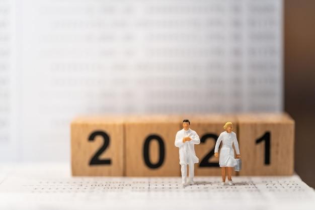 2021년 새해 비즈니스, 돈 계획 및 건강 관리 개념. 의사와 간호사 미니어처 그림 사람들은 나무 숫자 블록을 배경으로 은행 통장을 걷고 있습니다.