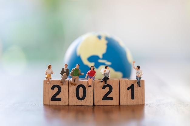 2021년 새해 비즈니스 팀 개념입니다. 미니 세계 공을 배경으로 나무 숫자 블록에 앉아 있는 사업가 및 사업가 미니어처 그림 사람들의 그룹입니다.