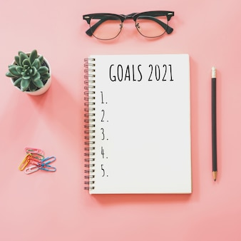 2021 new year concept. goals list in notepad, smartphone, stationery on pink pastel color with copy space
