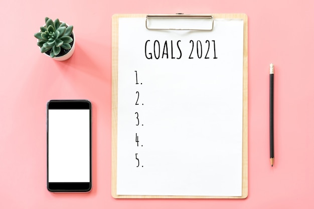 2021 new year concept. goals list in stationery, blank clipboard, smartphone, pot plant on pink pastel color with copy space