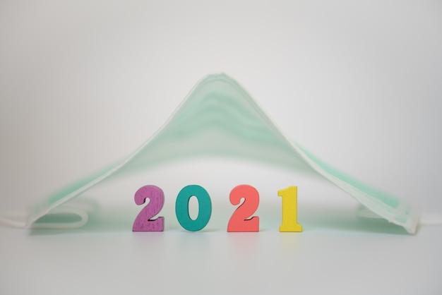 2021年の新年、covid-19およびhelathcareconcept。白い背景の上のサージカルフェイスマスクの下で木製のカラフルな番号のクローズアップ。
