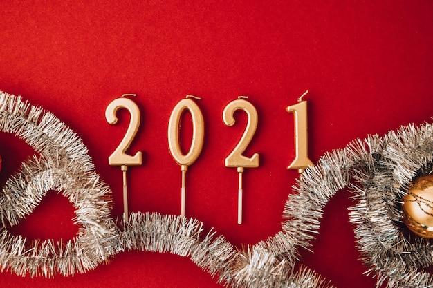2021 новогодний дизайн. дата выложена свечами возле ели на красном фоне с копией пространства. с рождеством, красные рождественские украшения. новогодние шары