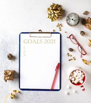 2021 new year goals. christmas decorations  with wish list text on notepad. flat lay