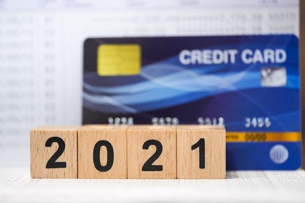 2021년 새해 계획 개념입니다. 나무 번호 블록을 닫으면 가짜 신용 카드로 은행 통장을 이겼습니다.