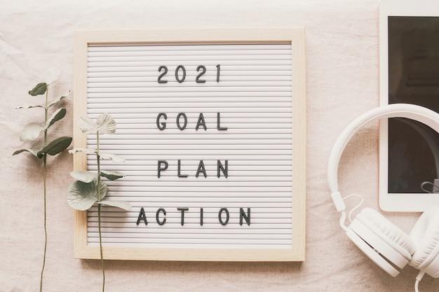 2021年の新年の抱負、目標、計画、タブレットとヘッドフォンを備えたレターボードでの行動