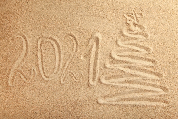 2021 new year text with christmas tree on sand background