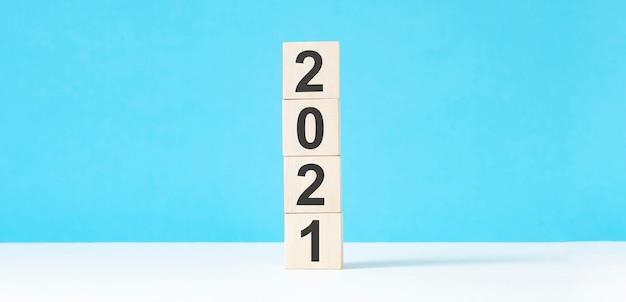 텍스트 복사 공간 블루 테이블 배경에 2021 새 해 나무 큐브. 비즈니스 목표, 미션, 해상도, 새해 새로운 개념