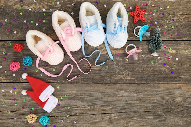 2021 new year written laces of children's shoes and pacifier on old wooden background.