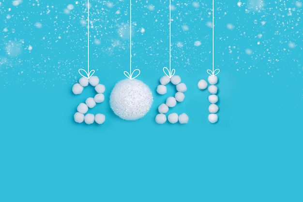2021 new years numbers made of white artificial snow and balls on a blue background