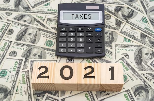 木製の立方体に「2021」。電卓のスコアボードの「税金」。財務コンセプト。税の概念。