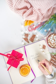 2021 유행성 해 새해 해상도 개념. 새로운 정상적인 covid 생활 목표, 크리스마스 장식, 핫 초콜릿이있는 새해 목표 및 해상도 배경 메모장