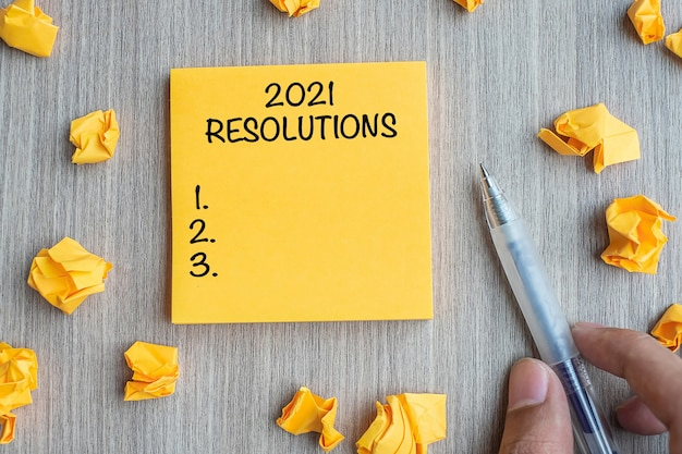 2021 resolutions word on yellow note with businessman holding pen and crumbled paper