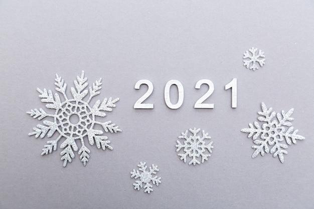 Серебряные числа 2021 года со снежинками на сером фоне. новый год и рождество концепция