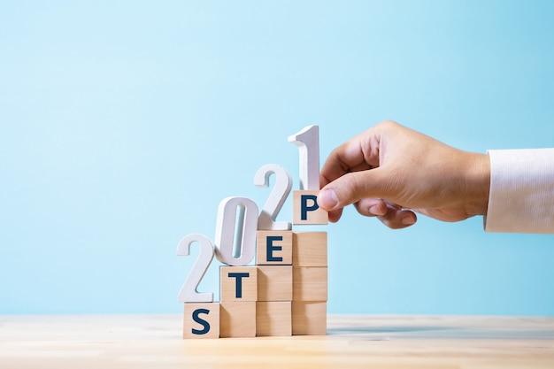 木箱の階段に番号とテキストを置く手で成功への2021年のステップ。事業計画と戦略