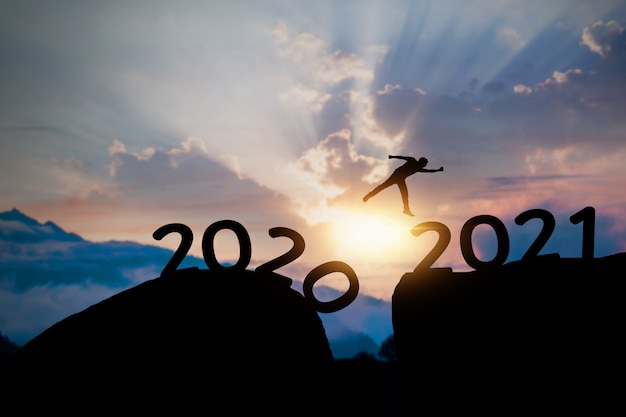 2021 success silhouette concept, man jumping to new year on top of mountain