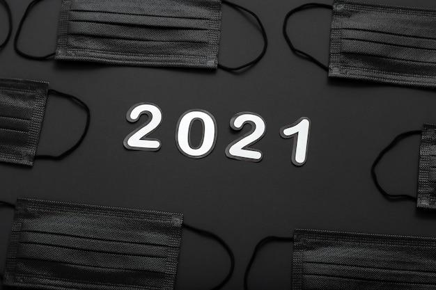 검은 의료 얼굴 마스크 패턴 프레임에 2021 텍스트 글자. covid lockdown의 2021 년 새해.