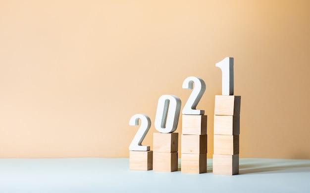 2021年のテキストは、パステルカラーの背景の木製のステップにモックアップします。