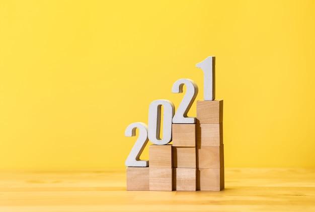 Текстовый макет 2021 года на деревянной ступеньке на цветном пастельном фоне.