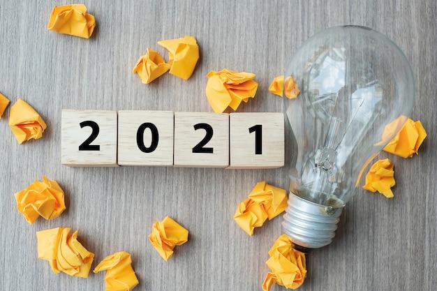 2021年のテキストの木製の立方体ブロックと電球付きの砕いた紙