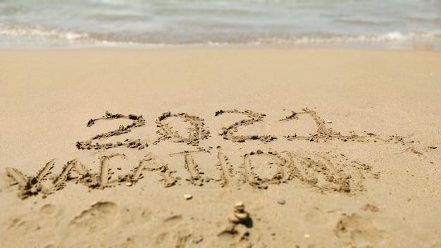 2021 휴가 바다 해변의 모래에 손으로 쓴 비문. 여름