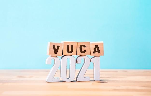 Концепции мира vuca 2021 года с текстом на деревянном блоке