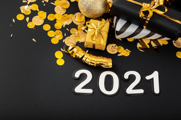 2021 white text on black background with golden confetti, christmas gift boxes. happy new year.