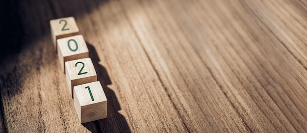 Деревянный блок 2021 года на деревянном столе и бетонная стена с солнечным светом из окна