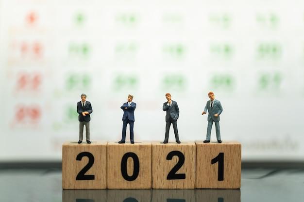 2021 년 비즈니스 및 계획 개념. 배경으로 달력 나무 숫자 블록에 서있는 사업가 미니어처 그림 사람들의 그룹입니다.