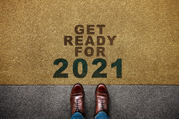 2021年のコンセプト。床に立っているビジネスマンの平面図です。新しい挑戦への一歩 Premium写真