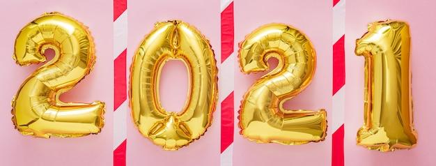 Золотые шары 2021 года с предупреждающей лентой на розовом. сохранение концепции социальной дистанции covid 19.