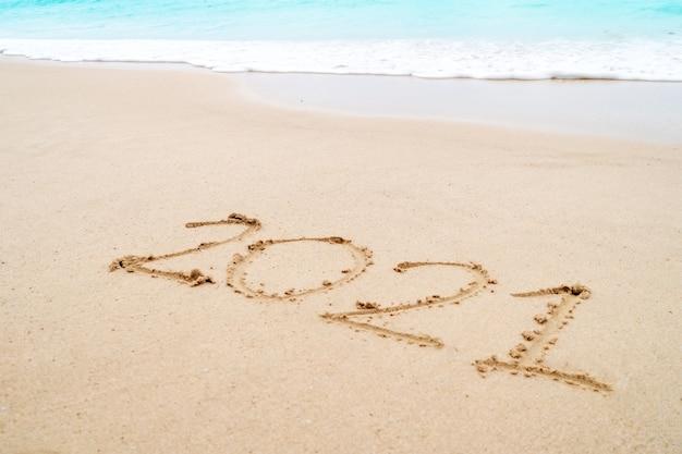 2021 year hand drawn on sand summer beach.