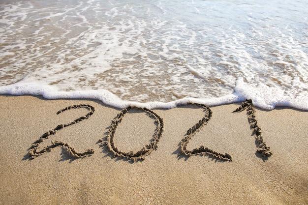 2021 год написано на песчаном пляже моря.