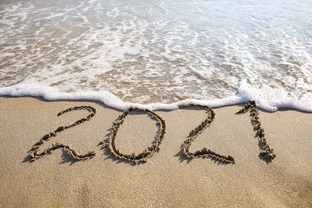 2021 year written on sandy beach sea.