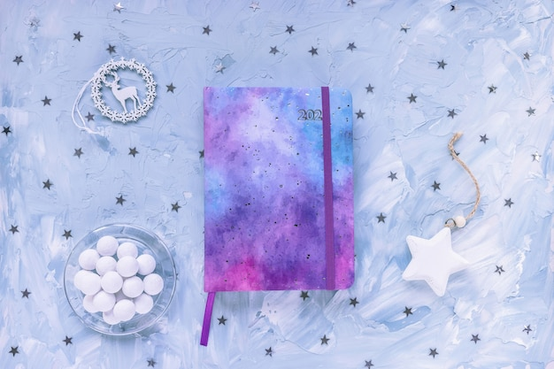 2021 yearly journal, chocolate and stars decoration on desk workspace, blue background.