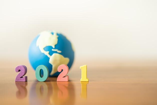 2021年、グローバルおよびビジネスコンセプト。木製のテーブルとコピー領域にミニの世界のおもちゃのボールでカラフルな木製の数のクローズアップ