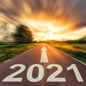 新年のコンセプトです。空のアスファルト道路の夕日と新年2021。
