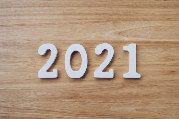 ビジネスとデザインコンセプト-木のテーブルに新年あけましておめでとうございますテキストの木製番号2021。