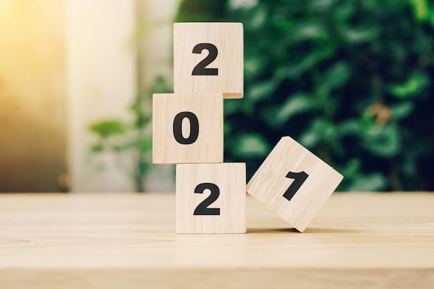 日光と木製のテーブルのウッドブロックに2021明けましておめでとう。新年のコンセプトです。